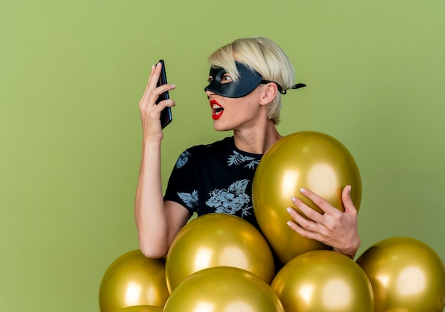 Jovem loira festeira com raiva usando máscara de baile de máscaras em pé atrás de balões, agarrando um deles segurando e olhando para o celular isolado em um fundo verde oliva com espaço de cópia