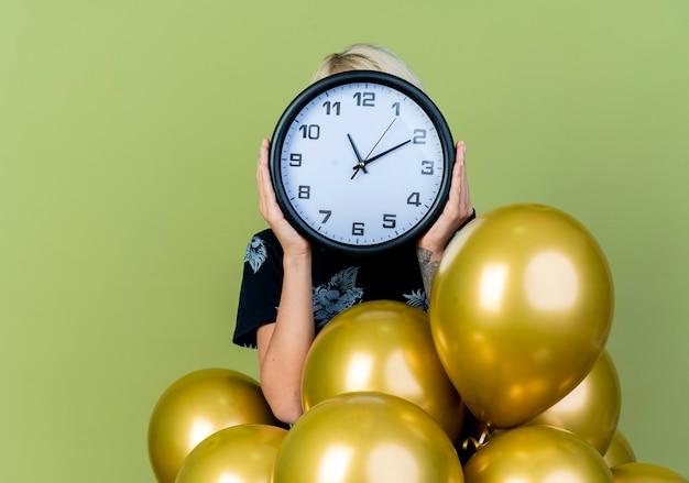 Jovem loira festeira em pé atrás de balões, segurando e se escondendo atrás de um relógio isolado em um fundo verde oliva com espaço de cópia