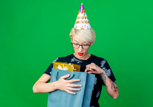 Jovem loira festeira impressionada com óculos e boné de aniversário segurando e olhando para dentro de um saco de papel com caixas de presente isoladas em um fundo verde com espaço de cópia