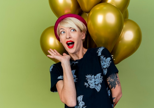 Jovem loira festeira impressionada com um chapéu de festa em pé na frente de balões, olhando para o lado, mostrando a mão vazia, isolada na parede verde oliva com espaço de cópia