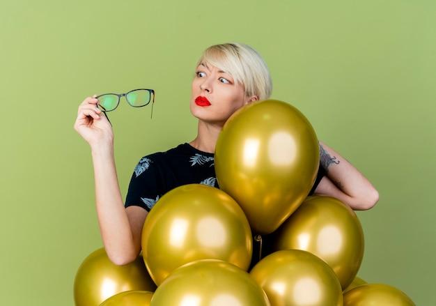 Jovem loira festeira impressionada em pé atrás de balões, segurando e olhando para copos isolados na parede verde oliva