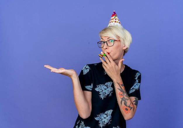 Jovem loira festeira, impressionada, usando óculos e boné de aniversário, olhando para a frente, segurando o soprador de festa na boca, mostrando a mão vazia isolada na parede roxa