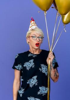 Jovem loira festeira, impressionada, usando óculos e boné de aniversário segurando balões, olhando para a frente, isolada na parede roxa