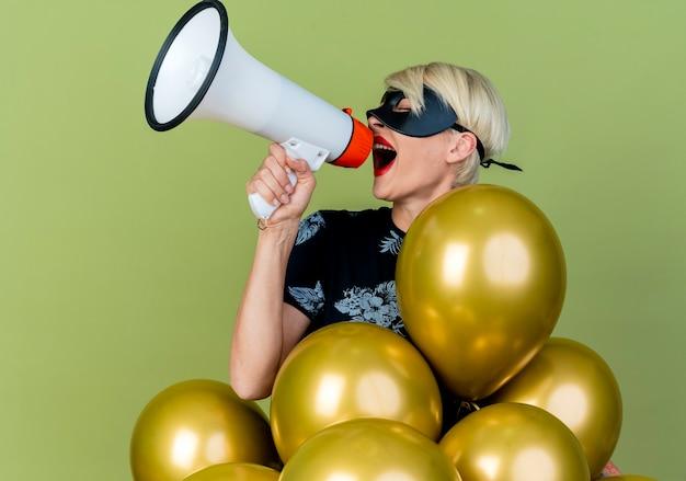 Jovem loira festeira usando máscara de baile de máscaras em pé atrás de balões, virando-se de frente para os lados, falando por alto-falante com os olhos fechados, isolado em um fundo verde oliva com espaço de cópia
