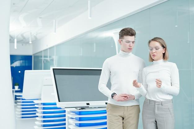 Jovem loira gerente de escritório consultando um cliente sobre o novo tablet digital transparente enquanto mostra como ele funciona
