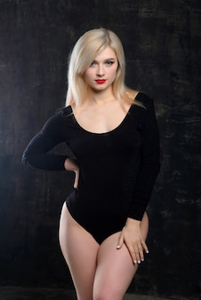 Jovem loira gorda com maquiagem brilhante em um macacão preto posando