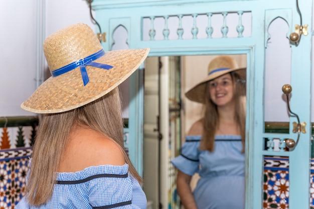 Jovem loira grávida com um vestido azul, experimentando um chapéu na frente de um espelho.