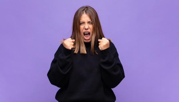 Jovem loira gritando agressivamente com olhar irritado, frustrado e irritado e punhos cerrados, sentindo-se furiosa