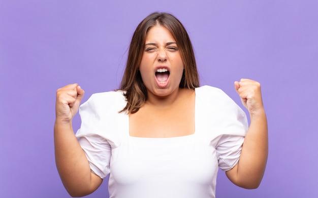 Jovem loira gritando agressivamente com uma expressão de raiva ou com os punhos cerrados celebrando o sucesso