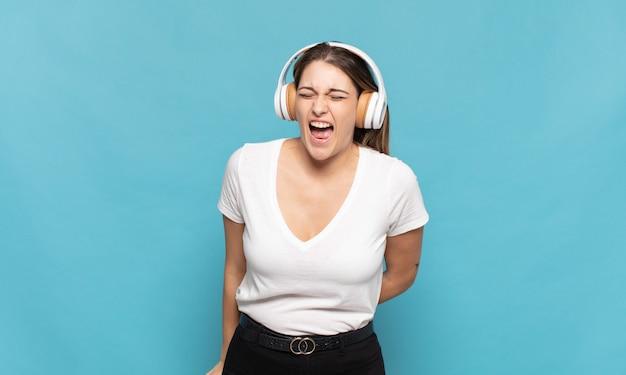 Jovem loira gritando agressivamente, parecendo muito zangada, frustrada, indignada ou irritada, gritando não