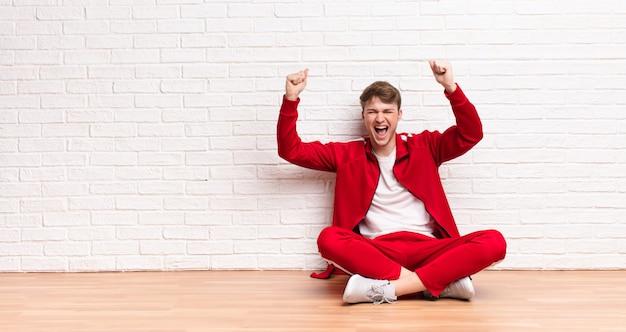 Jovem loira gritando triunfantemente, parecendo vencedor animado, feliz e surpreso, comemorando sentado no chão