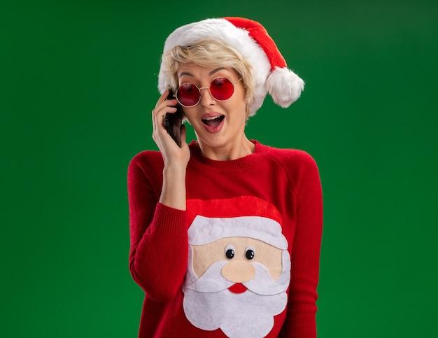 Jovem loira impressionada com chapéu de natal e suéter de natal de papai noel com óculos falando ao telefone, olhando para baixo isolado no fundo verde