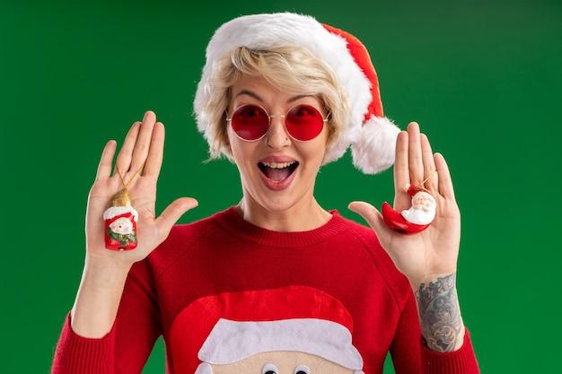 Jovem loira impressionada com chapéu de natal e suéter de natal de papai noel com óculos olhando mostrando boneco de neve e papai noel enfeites de natal isolados na parede verde