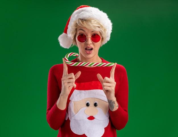 Jovem loira impressionada com chapéu de natal e suéter de natal de papai noel com óculos, olhando para a câmera segurando um bastão de doce de natal isolado no fundo verde