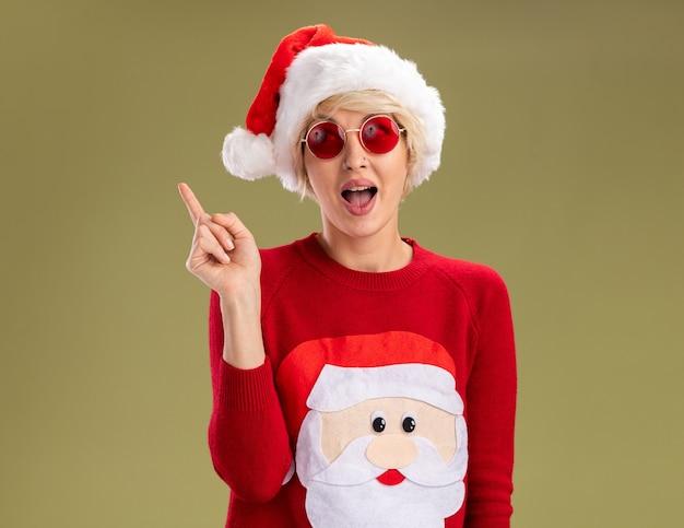 Jovem loira impressionada com chapéu de natal e suéter de natal de papai noel com óculos olhando para o lado apontando para cima isolado no fundo verde oliva