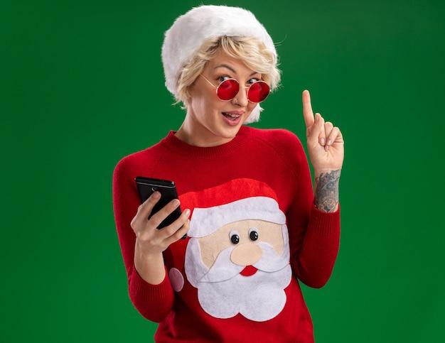Jovem loira impressionada com chapéu de natal e suéter de natal de papai noel com óculos segurando um celular olhando e apontando para cima, isolado na parede verde com espaço de cópia