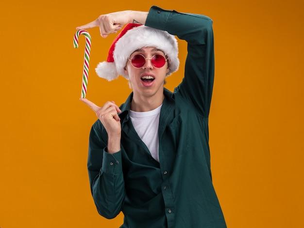 Jovem loira impressionada com chapéu de papai noel e óculos segurando uma bengala de natal verticalmente, olhando para a câmera isolada em um fundo laranja com espaço de cópia