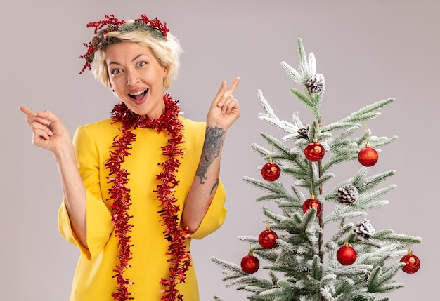 Jovem loira impressionada com coroa de flores de natal e guirlanda de ouropel em volta do pescoço em pé perto da árvore de natal decorada, olhando para a câmera apontando para cima