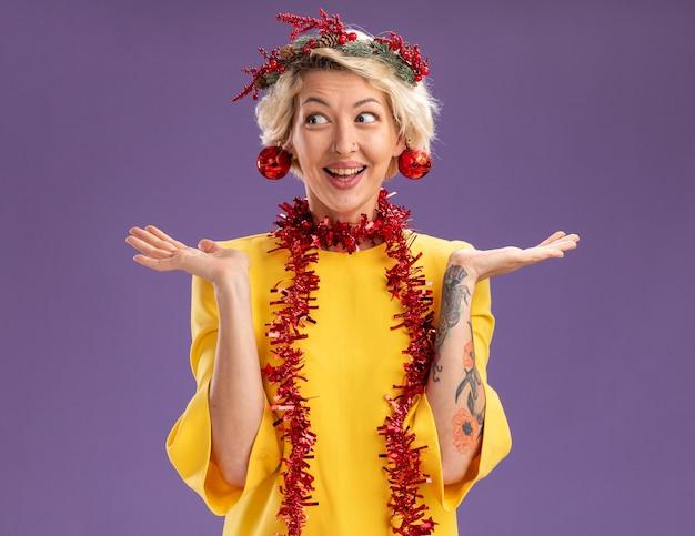Jovem loira impressionada com coroa de flores de natal e guirlanda de ouropel em volta do pescoço, olhando para o lado, mostrando as mãos vazias com enfeites de natal pendurados em suas orelhas isoladas no fundo roxo