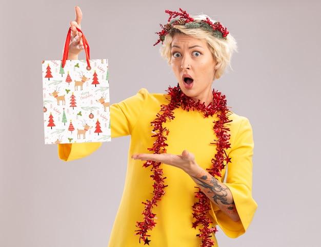 Jovem loira impressionada com coroa de flores de natal e guirlanda de ouropel em volta do pescoço segurando e apontando com a mão para a sacola de presente de natal, olhando para a câmera, isolada no fundo branco