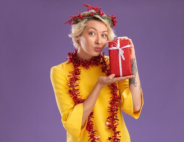 Jovem loira impressionada com coroa de flores de natal e guirlanda de ouropel em volta do pescoço segurando um pacote de presente, olhando para a câmera com os lábios franzidos, isolados no fundo roxo