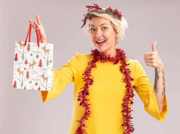 Jovem loira impressionada com coroa de flores de natal e guirlanda de ouropel em volta do pescoço, segurando uma sacola de presente de natal, olhando para a câmera mostrando o polegar isolado no fundo branco