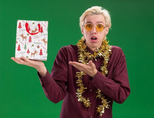 Jovem loira impressionada de óculos com guirlanda de ouropel no pescoço segurando uma sacola de presente de natal apontando para ela, olhando para a câmera isolada sobre fundo verde