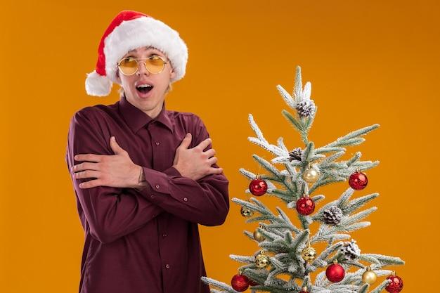 Jovem loira impressionada e fria com chapéu de papai noel e óculos em pé perto da árvore de natal decorada em fundo laranja