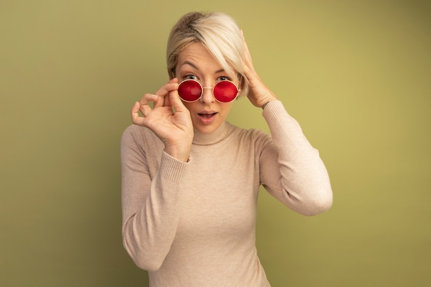 Jovem loira impressionada usando e agarrando óculos de sol, olhando colocando a mão na cabeça isolada em uma parede verde oliva com espaço de cópia
