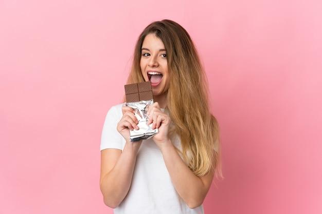 Jovem loira isolada comendo uma tablete de chocolate