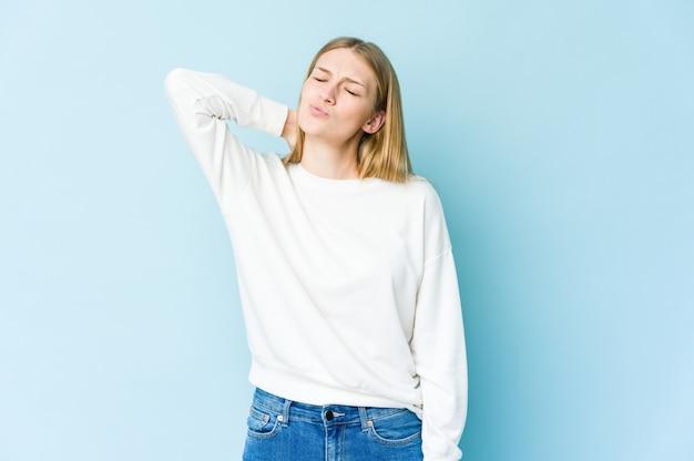 Jovem loira isolada em azul, tendo uma dor no pescoço devido ao estresse, massageando e tocando com a mão.