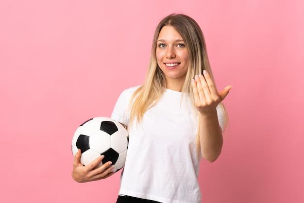 Jovem loira isolada em rosa com uma bola de futebol e fazendo o gesto de aproximar