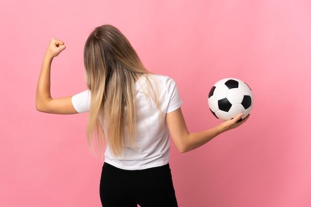 Jovem loira isolada em rosa com uma bola de futebol