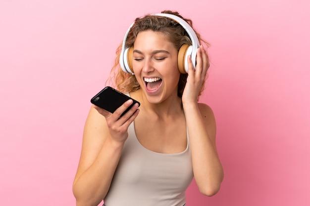 Jovem loira isolada em um fundo rosa ouvindo música com um celular e cantando