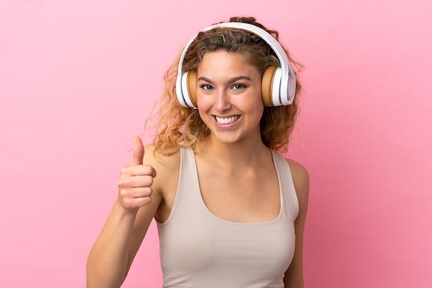 Jovem loira isolada em um fundo rosa ouvindo música e com o polegar para cima