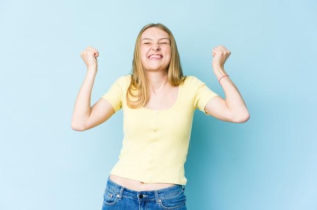 Jovem loira isolada na parede azul comemorando vitória, paixão e entusiasmo