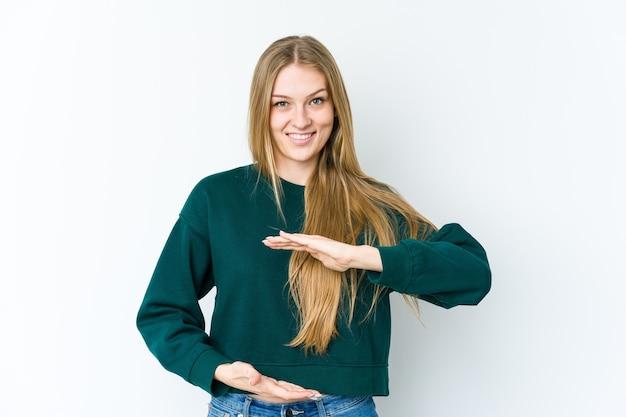 Jovem loira isolada na parede branca segurando algo com as duas mãos