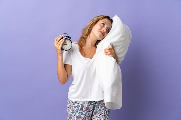 Jovem loira isolada na parede roxa de pijama segurando o relógio e o travesseiro com uma expressão feliz