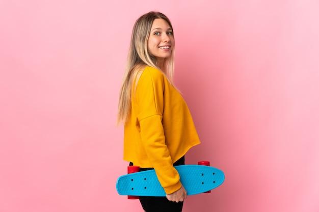 Jovem loira isolada na rosa com um skate