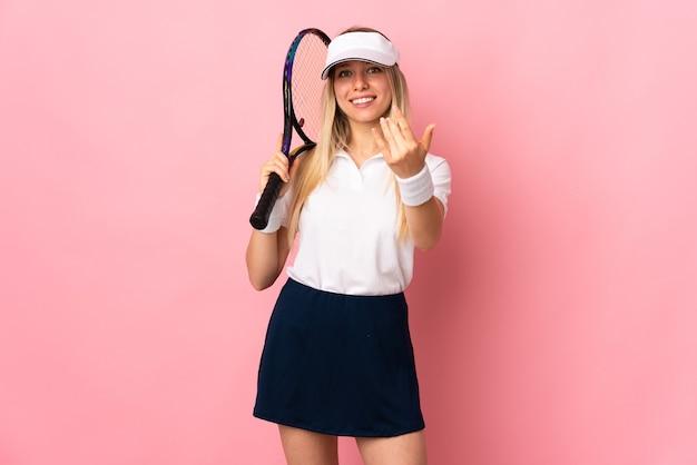 Jovem loira isolada na rosa jogando tênis e fazendo gestos de aproximação
