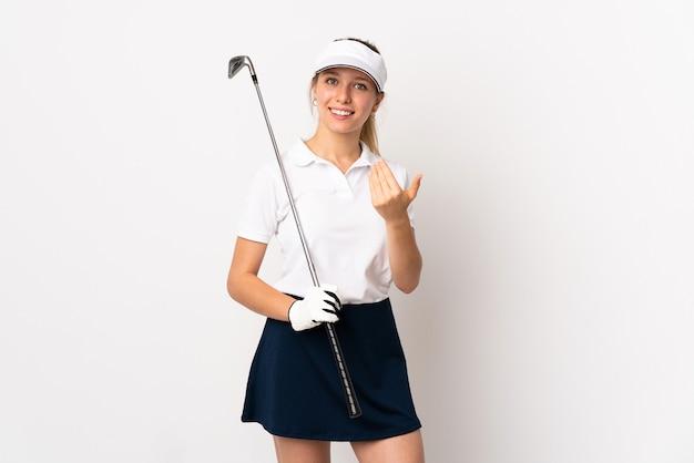 Jovem loira isolada no fundo branco jogando golfe e fazendo gesto de aproximar