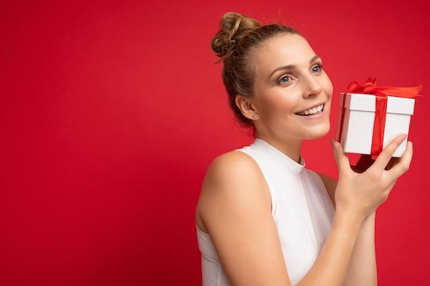 Jovem loira isolada sobre a parede de fundo vermelho, vestindo blusa branca, segurando a caixa de presente e olhando para o lado. copiar espaço, maquete