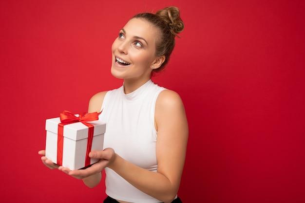 Jovem loira isolada sobre a parede de fundo vermelho, vestindo top branco, segurando a caixa de presente e olhando para o lado e pensando. espaço vazio