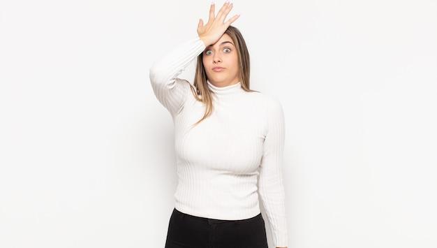 Jovem loira levantando a palma da mão na testa pensando oops, depois de cometer um erro estúpido ou lembrar, sentindo-se idiota