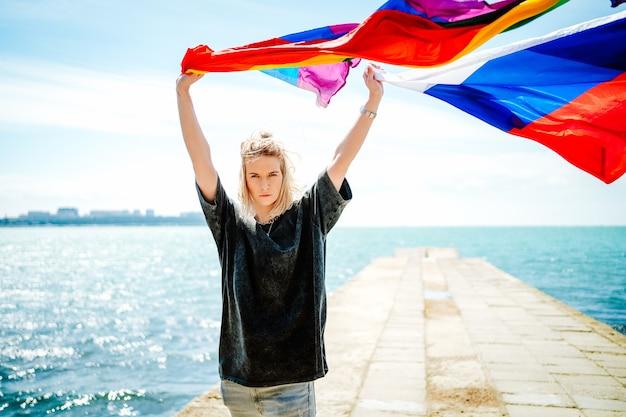 Jovem loira linda corta a bandeira do arco-íris e a bandeira da rússia nas mãos contra o mar. foto de alta qualidade
