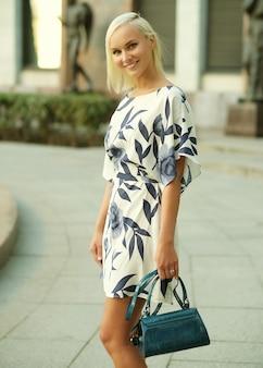 Jovem loira linda usando vestido e andando na rua