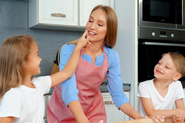 Jovem loira, mãe e filhos se divertindo enquanto cozinham massa