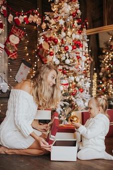 Jovem loira mãe e suas filhas em roupas de malha brancas, abrindo um presente de natal mágico por uma árvore de natal na acolhedora sala de estar no inverno
