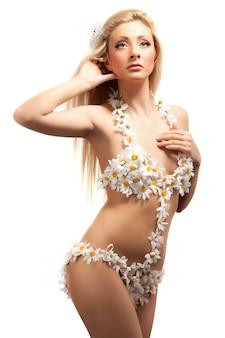 Jovem loira magra com fantasia de baixo peso feita de flores de camomila em pé sobre um fundo branco