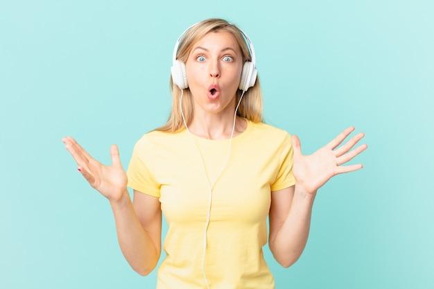 Jovem loira maravilhada, chocada e atônita com uma surpresa inacreditável e ouvindo música.